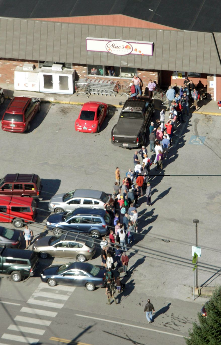 CUSTOMERS: Residents wait outside the grocery store in Rochester, Vt., inaccessible since Tropical Storm Irene hit. It is one of many small towns in the state to receive supplies Tuesday via a National Guard airlift. (Associated Press)