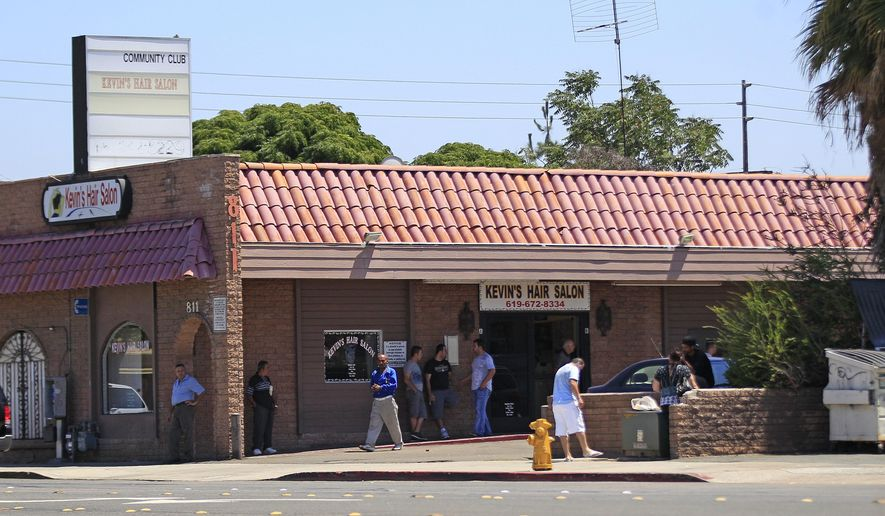 A group of men stand outside the building at 811 E. Main St. in El Cajon, Calif., Thursday, Aug. 18, 2011. The community club listed on the marquee is the location mentioned in criminal charges where various law enforcement agents purchased narcotics, firearms, and explosive devices in Operation Shadow Box. (AP Photo/Lenny Ignelzi)