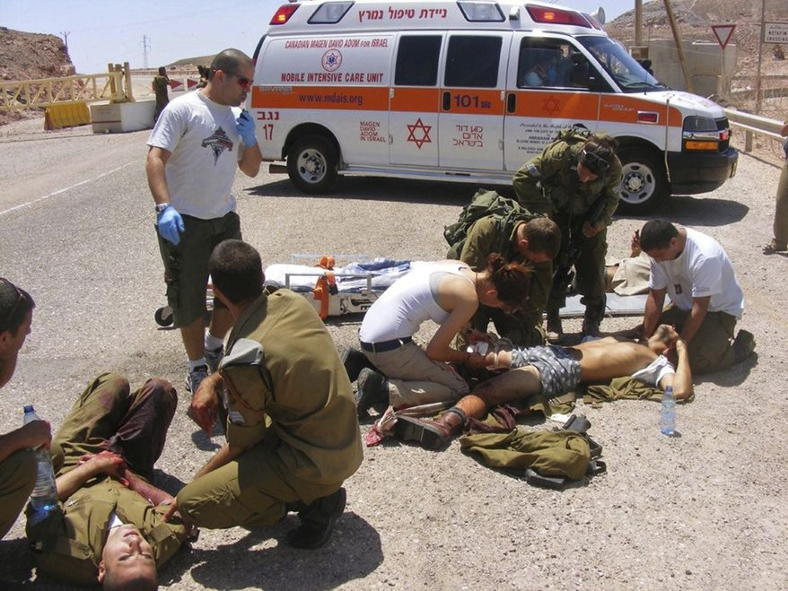 ** FILE ** Wounded Israeli soldiers are treated at the site of a shooting attack along the border between Israel and Egypt, southern Israel, Thursday, Aug. 18, 2011. (AP Photo/Yosi Ben)