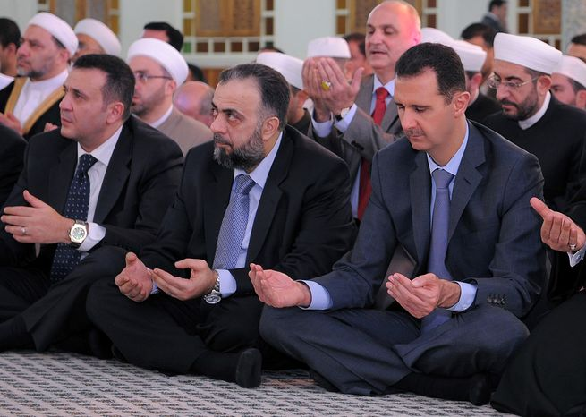 Syrian President Bashar Assad (right) prays during a service for Eid al-Fitr, which marks the end of Ramadan, at the Hafez Assad Mosque in Damascus, Syria, on Tuesday, Aug. 30, 2011. (AP Photo/SANA)