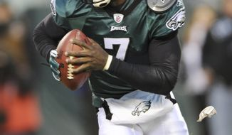 ** FILE ** In this Jan. 9, 2011, photo, Philadelphia Eagles quarterback Michael Vick (7) runs from a tackler during the first half of an NFL wild card playoff football game against the Green Bay Packers in Philadelphia. (AP Photo/Michael Perez)