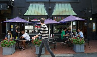 Patrons eat out on the sidewalk patio of the Hawk 'n' Dove bar in Capitol Hill on Wednesday, Aug. 31, 2011. After more than 40 years in business, the bar, which has been an institution on Capitol Hill will be closing down Oct. 2. There will be a series of events and celebrations leading up to the closing, and all of the bar's contents will be auctioned off. Regular patrons told The Washington Times that they are saddened by the closing. Many consider it a home away from home where they gather with friends. (Barbara L. Salisbury/The Washington Times)