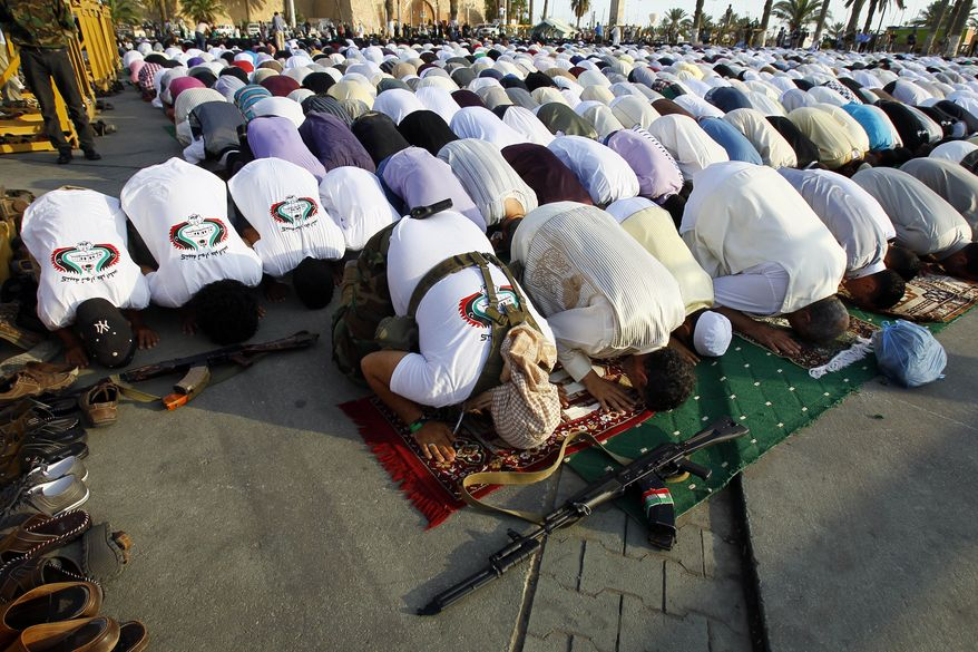 Libyans pray in Martyr's Square, formerly known as Green Square, during the morning Eid prayer marking the end of the Muslim holy month of Ramadan, in Tripoli, Libya, on Wednesday, Aug. 31, 2011. (AP Photo/Francois Mori)