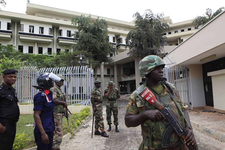 """** FILE ** Nigerian soldiers and police stand guard outside U.N. headquarters in Abuja, Nigeria on Aug. 27, 2011, a day after a suicide bomber crashed through an exit gate and detonated a car full of explosives in the reception area. The country's president has vowed his government will bring terrorism """"under control. (AP Photo/Rebecca Blackwell)"""