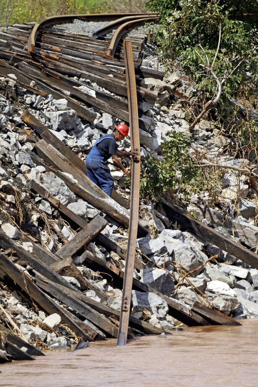A worker attaches a chain to a washed-out rail line in Phoenicia, N.Y., in the Catskill Mountains. Gov. Andrew Cuomo said Irene caused $1 billion in damage in New York, most of it from flooding upstate.