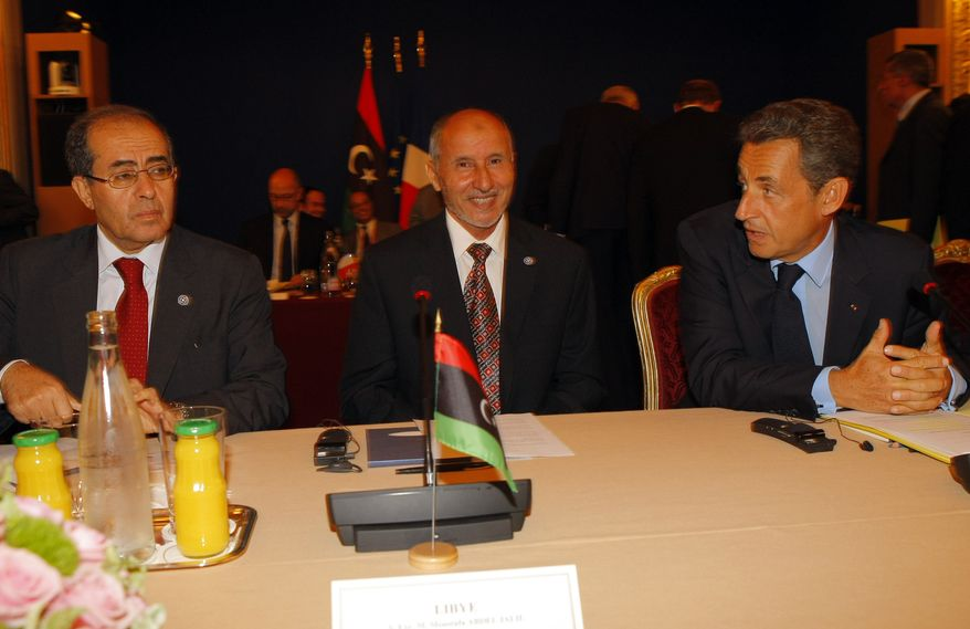 French President Nicolas Sarkozy (right) talks with Libyan National Transitional Council Chairman Mustafa Abdel Jalil (center) and Libyan Transitional National Council Prime Minister Mahmoud Jibril at the Elysee Palace in Paris on Thursday, Sept. 1, 2011. Heads of state and top officials gathered in the French capital to work out how to support Libya's opposition leaders after Col. Moammar Gadhafi's fall from power. (AP Photo/Jacques Brinon)