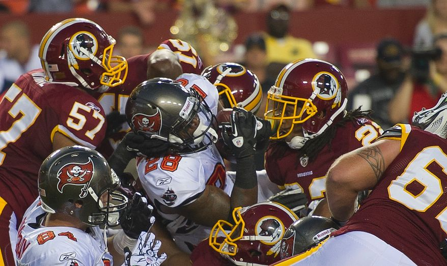 Kregg Lumpkin of the Tampa Bay Buccaneers (28) is stopped by the Redskin defense in the first quarter at FedEx Field in Landover, Md., Thursday, September 1, 2011, in the last pre-season game. (Rod Lamkey Jr./The Washington Times)