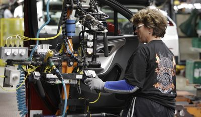 ** FILE ** In this July 27, 2011, photo, assembly line worker Sarah Lowidon moves a door into position for a Chevrolet Volt at the General Motors Hamtramck Assembly plant in Hamtramck, Mich. (AP Photo/Paul Sancya)