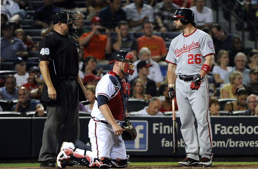 ASSOCIATED PRESS Washington Nationals batter Jesus Flores (26) looks to home plate umpire Mark Carlson, left, as Flores strikes out with bases loaded in the eight inning of their baseball game Thursday, Sept. 1, 2011, at Turner Field in Atlanta, as Braves catcher Brian McCann waits behind the plate. Atlanta won the game 5-2.