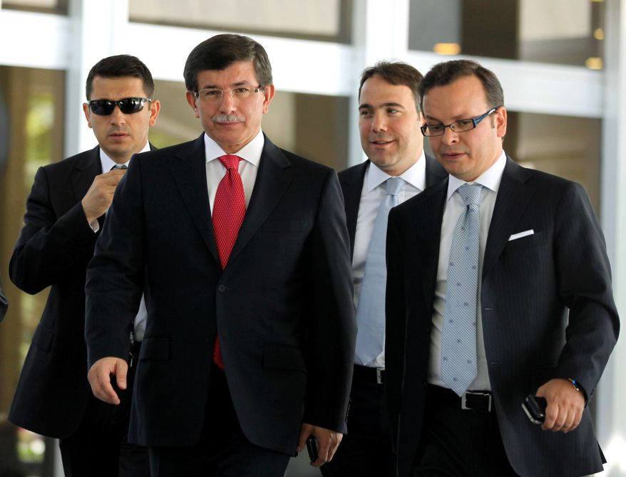 Turkish Foreign Minister Ahmet Davutoglu (center left) leads advisers as he arrives to speak to the media in Ankara, Turkey, on Sept. 2, 2011. (Associated Press)