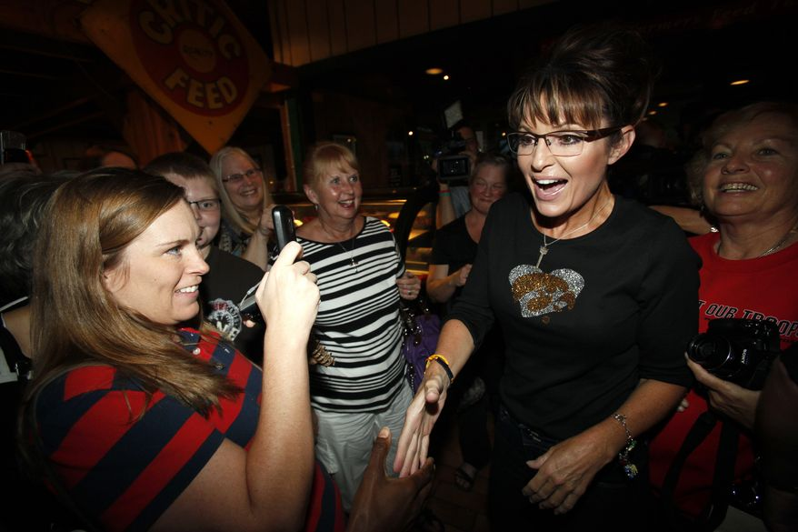Former Alaska Gov. Sarah Palin greets supporters at The Machine Shed restaurant, in Urbandale, Iowa, Friday, Sept. 2, 2011. (AP Photo/Charlie Neibergall)