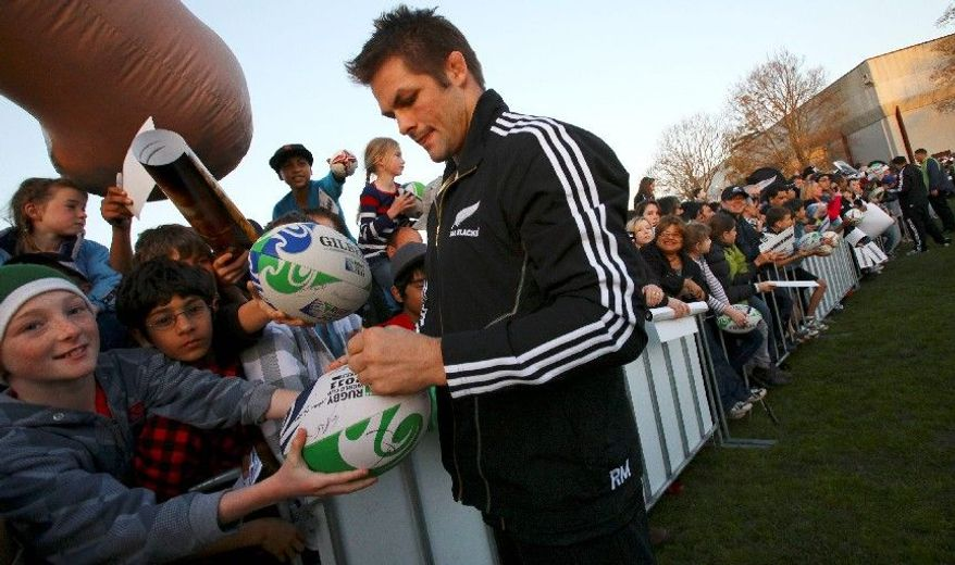 ASSOCIATED PRESS PHOTOGRAPHS New Zealand All Blacks captain Richie McCaw signs his name on a rugby ball for a child during a fan event Sunday ahead of the seven-week Rugby World Cup in Auckland, New Zealand. In a country of 4 million, rugby has been the most important game for more than 100 years.