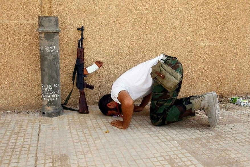 ASSOCIATED PRESS MOMENT OF PEACE: A Libyan rebel prays Sunday outside an complex where rockets and shells were found. Internet postings by jihadists among the rebels reveal plotting to create an Islamic state.
