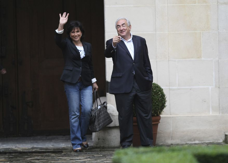 Dominique Strauss-Kahn (right), former head of the International Monetary Fund, and his wife, Anne Sinclair, gesture to the media upon their arrival at their home in Paris on Sunday, Sept. 4, 2011. (AP Photo/Jacques Brinon)