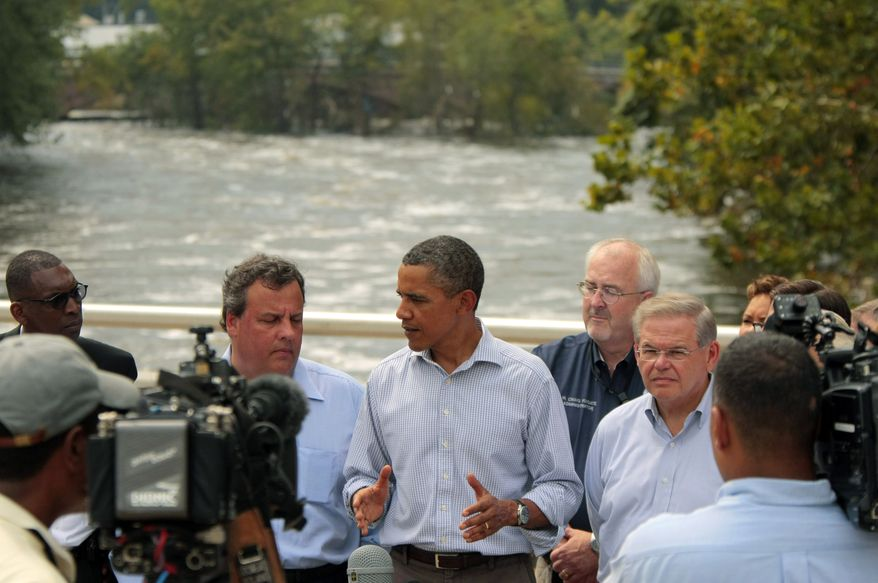 President Obama (center) talks to reporters on the Temple Street Bridge over the Passaic River as he visits areas damaged by Hurricane Irene on Sunday, Sept. 4, 2011, in Paterson, N.J. Gov. Chris Christie stands left of Mr. Obama. (AP Photo/John O'Boyle, Pool)