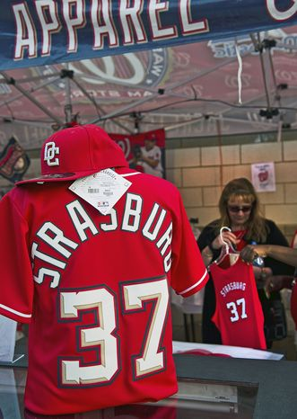 """Annette Alvarado-Bernal, of Puerto Rico, buys a Strasburg tank top for a visiting family member at Nationals Stadium on Friday. """"I have my own,"""" says Ms. Alvarado-Bernal, who adds she is a huge Strasburg fan, but """"I'm recruiting more."""""""