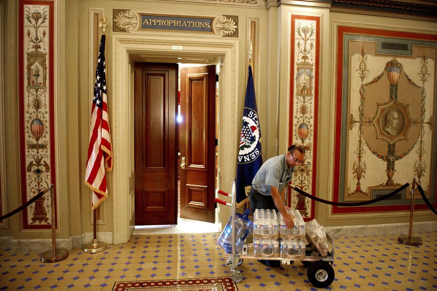 Senate Facilities Services technician Carlos Abarca delivers cases of bottled water to the Appropriations Committee in July. One internal cost-saving measure Congress hasn't yet availed itself of is to opt instead for D.C. tap water. (Rod Lamkey Jr./The Washington Times)