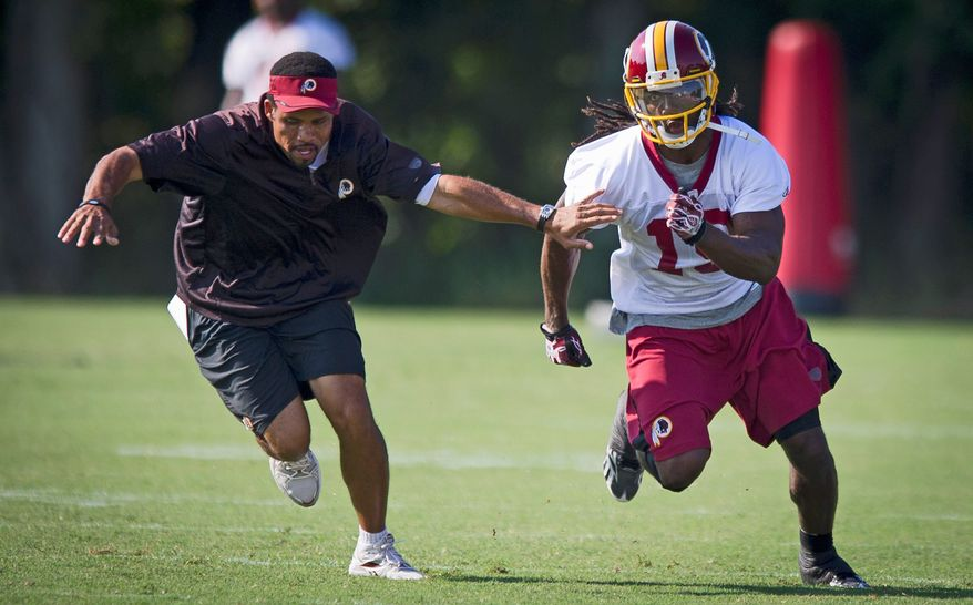 Washington Redskins wide receiver Donte Stallworth (19) gets past wide receivers coach Keenan McCardell during drills, during training camp at Redskins Park in Ashburn, Va, Wednesday, August 10, 2011. (Rod Lamkey Jr./The Washington Times)