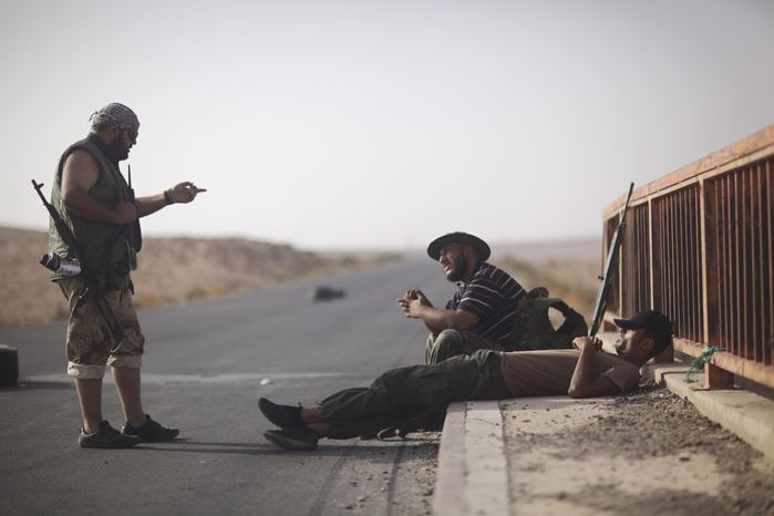 Rebel fighters chat at a checkpoint between Tarhouna and Bani Walid, Libya, on Tuesday, Sept. 6, 2011. Col. Moammar Gadhafi is determined to fight his way back to power, the toppled dictator's spokesman said Tuesday, but a large convoy of his soldiers apparently has deserted, crossing the Libyan desert into neighboring Niger. (AP Photo/Alexandre Meneghini)