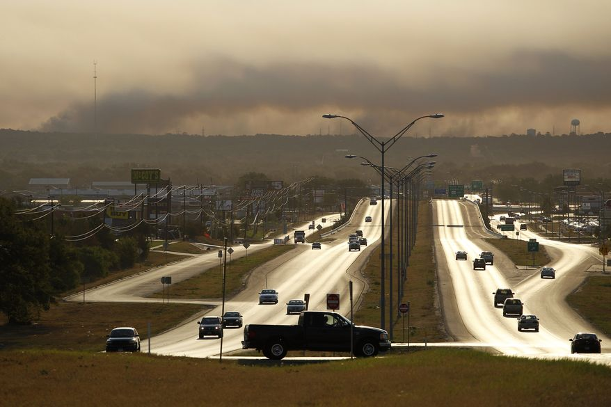 Smoke from a wildfire hangs in the sky on Tuesday, Sept. 6, 2011, in Bastrop, Texas. Officials hope calmer winds will help firefighters battling the fires, which have destroyed nearly a thousand homes in the state in the past week. (AP Photo/Eric Gay)