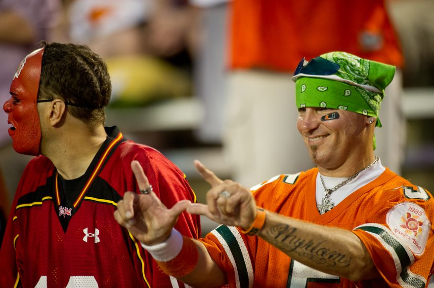 A Maryland Terrapins fan and a Miami Hurricanes fan stand together before the start of the game in college football at Byrd Stadium at the University of Maryland, on Monday September 5, 2011. (Andrew Harnik / The Washington Times)