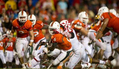 Defensive lineman Clarence Murphy (98) of the Maryland Terps tackles running back Lamar Miller (6) of the Miami Hurricanes in college football at Byrd Stadium at the University of Maryland in College Park, MD, Monday September 5, 2011. (Andrew Harnik / The Washington Times)