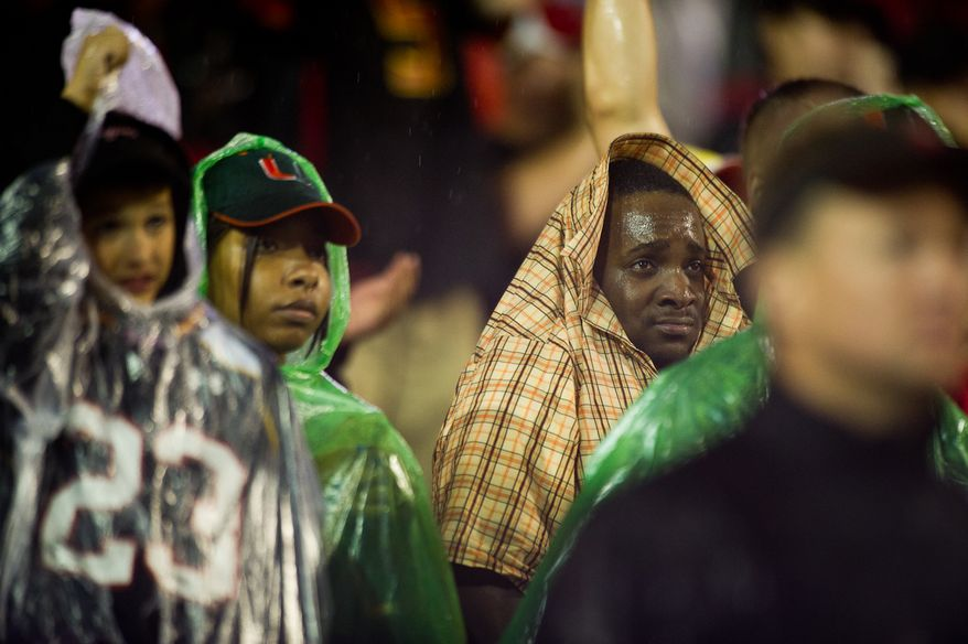 A wet fan tries to shield himself from heavy rain during the game between the Maryland Terps and the Miami Hurricanes in college football at Byrd Stadium at the University of Maryland in College Park, MD, Monday September 5, 2011. (Andrew Harnik / The Washington Times)