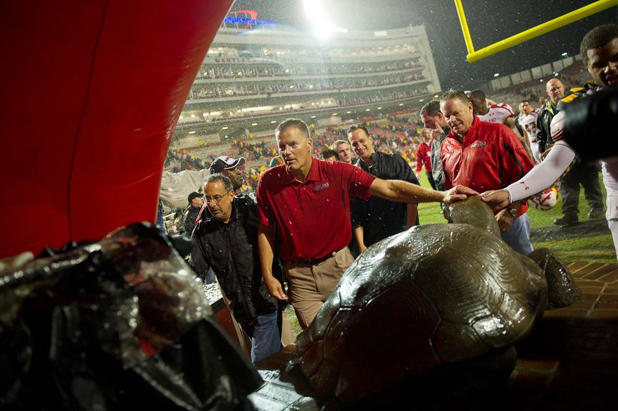 Maryland Head Coach Randy Edsall rubs the head of a bronze Terrapin, the school mascot, after a 32-24 win over the Miami Hurricanes at Byrd Stadium at the University of Maryland in College Park, MD, Monday September 5, 2011. (Andrew Harnik / The Washington Times)