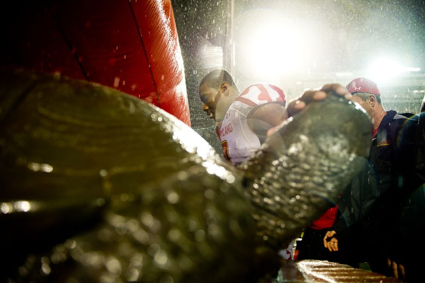 Maryland linebacker Demetrius Hartsfield (9) rubs the head of a bronze Terrapin, the school mascot, after a 32-24 win over the Miami Hurricanes at Byrd Stadium at the University of Maryland in College Park on Monday, Sept. 5, 2011. (Andrew Harnik/The Washington Times)