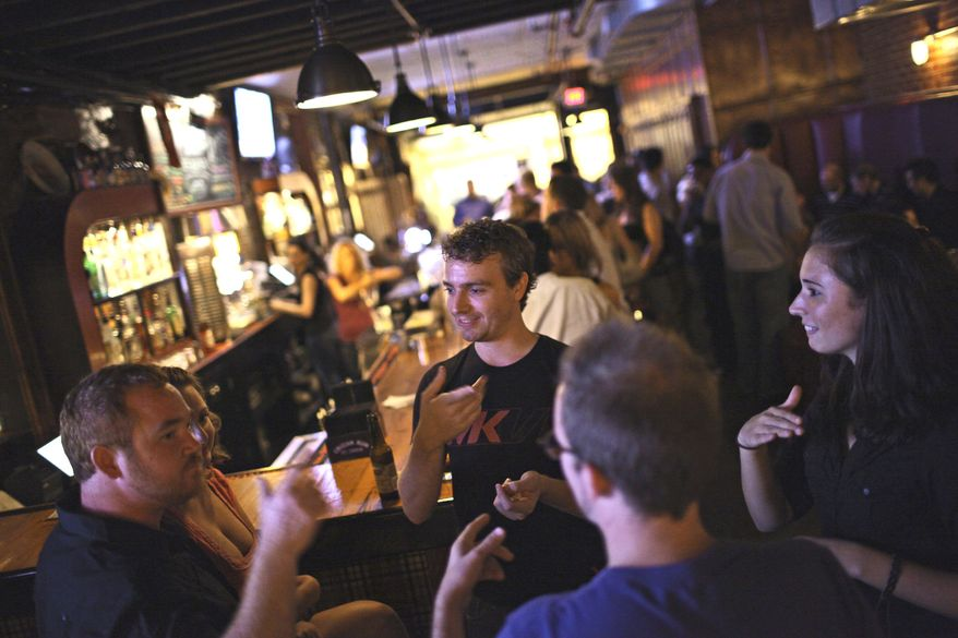 Hearing-impaired friends (from left) Michael Baker, Kenny Berrigan, Chris Kearney and Alicia Balzer hang out at H Street Country Club. (Andrew Harnik/The Washington Times)
