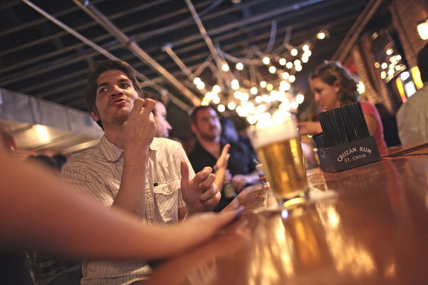 "Student Ross Cooper signs with a friend at H Street Country Club. Bartenders have learned to sign bar basics, such as ""beer"" and ""wine."" Brighter lights make it easier to see sign language and read lips. (Andrew Harnik/The Washington Times)"
