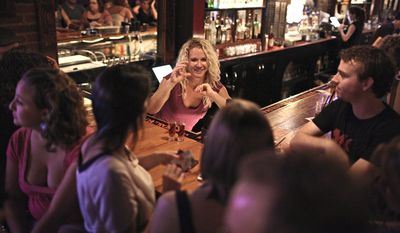 HELPING HANDS: Bartender Leah Mackie has learned to sign bar-specific words, the alphabet and the lyrics to a few songs so she can communicate with her hearing-impaired patrons at H Street Country Club in Northeast. (Andrew Harnik/The Washington Times)