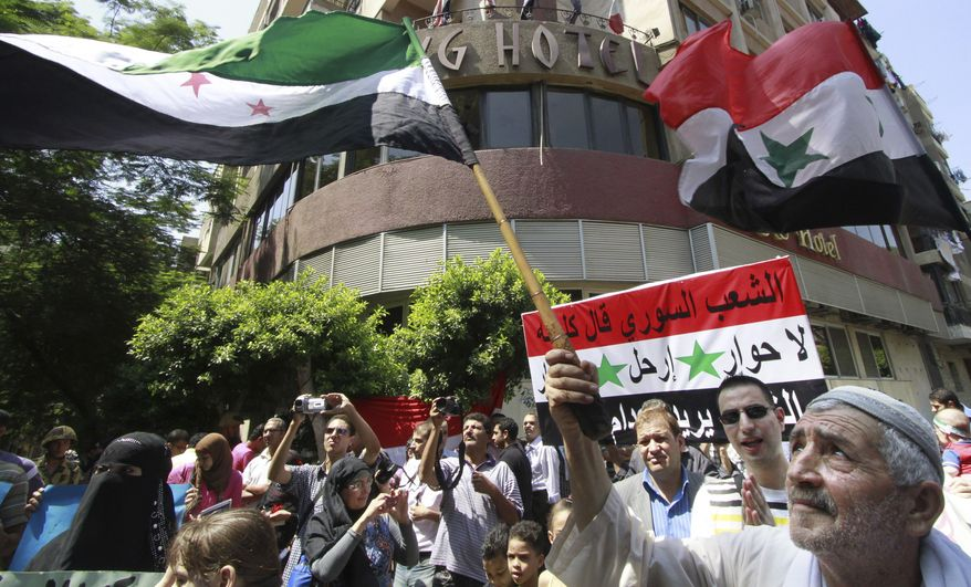 """An anti-Syrian-regime protester waves a Syrian revolutionary flag during a demonstration in Cairo on Tuesday, Sept. 6, 2011, to show support for Syrian protesters. The Arabic placard reads, """"Syrian people say: No for talks, get out."""" (AP Photo)"""