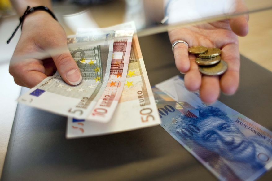 **FILE** This photo from June 8, 2011, shows a woman changing Swiss francs to Euro at a counter in Kreuzlingen, Switzerland. (Associated Press/Keystone)