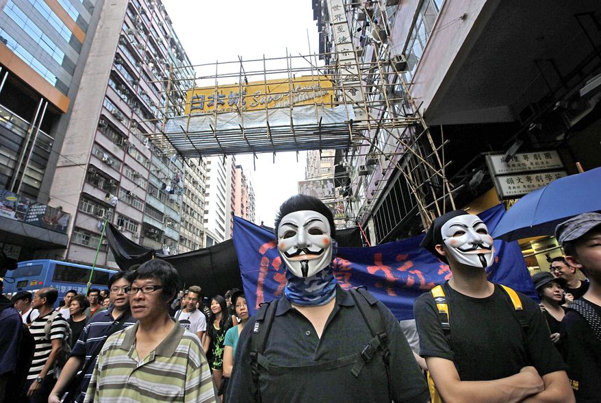 """ASSOCIATED PRESS Protesters wear Guy Fawkes masks as they march through downtown Hong Kong on Sept. 3 because they believe Hong Kong police ratcheted up security and tightened restrictions on the media and protesters during a recent visit by China's vice premier. """"People are very concerned that their freedoms are being undermined,"""" pro-democracy legislator Emily Lau said. """"The whole city is angry."""""""