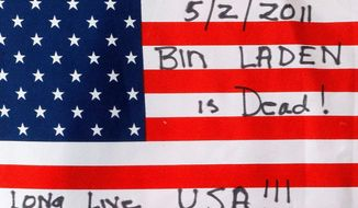 ASSOCIATED PRESS PHOTOGRAPHS A flag noting the killing of Osama bin Laden is placed at the temporary memorial in Shanksville, Pa., to the pasengers who were killed while stopping terrorists aboard United Airlines Flight 93 on May 2.
