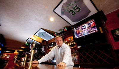 """Jerseys with the names of firefighters who were killed in the terrorist attacks 10 years ago hang above the bar at Paul Hurley's restaurant, P.D. O'Hurley's, at 72nd and Broadway in New York. """"You still think those  guys are going to walk through that door,"""" Mr. Hurley said."""