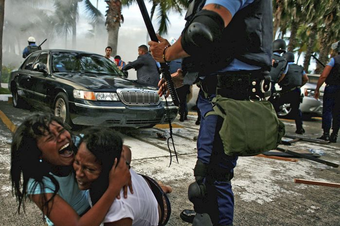 Associated Press photographs High school student demonstrator Eliza Ramos (left) hangs on to mother Betty Pena after anti-riot police fired tear gas to disperse a student protest against budget cuts in front of the Capitol building in San Juan, Puerto Rico, in June 2010. The police force in Puerto Rico has unnecessarily injured hundreds of people and killed numerous others, the U.S. Justice Department's Civil Rights Division said in a 116-page report released Thursday.