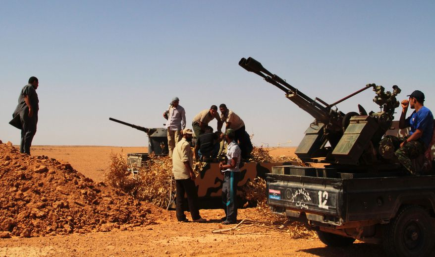 Rebel fighters take control of a military vehicle, center, positioned to defend what used to be Gadhafi's 32nd infantry regiment's base at Mardun, some 10 kilometers from the outskirts of Ban Walid, Libya, Wednesday, Sept. 7, 2011. (AP Photo/Gaia Anderson)