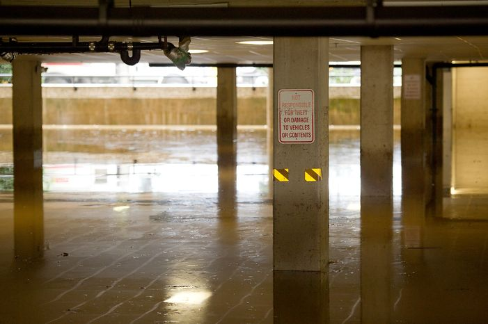 """A sign reading """"Not responsible for theft or damage to vehicles or contents"""" is seen in the basement parking lot at Alexandria Tech Center 4 on Eisenhower Avenue in Alexandria, Va., on Sept. 9, 2011. The lot was flooded after heavy rains pounded the region the previous night. (Andrew Harnik/The Washington Times)"""