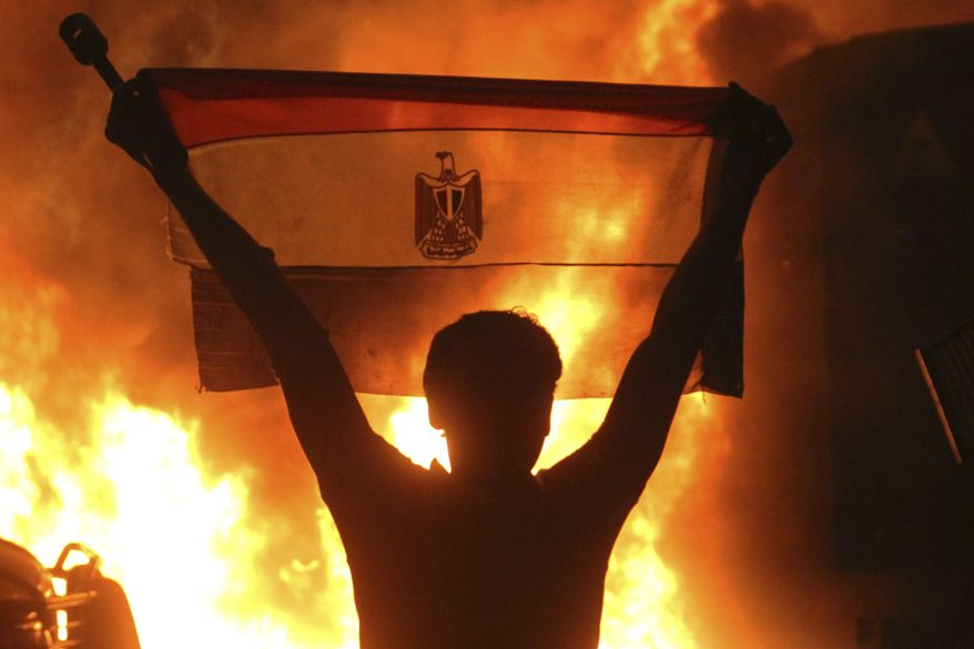 A protester holds the Egyptian national flag as a fire rages outside the building housing the Israeli embassy in Cairo, Egypt, Friday, Sept. 9, 2011. (AP Photo)