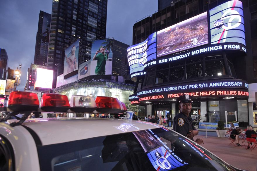A police officer stands guard in New York's Times Square on Sept. 9, 2011, as the ABC news ticker displays news of a credible but unconfirmed al Qaeda threat to use a car bomb on bridges or tunnels in New York City or D.C. (Associated Press)