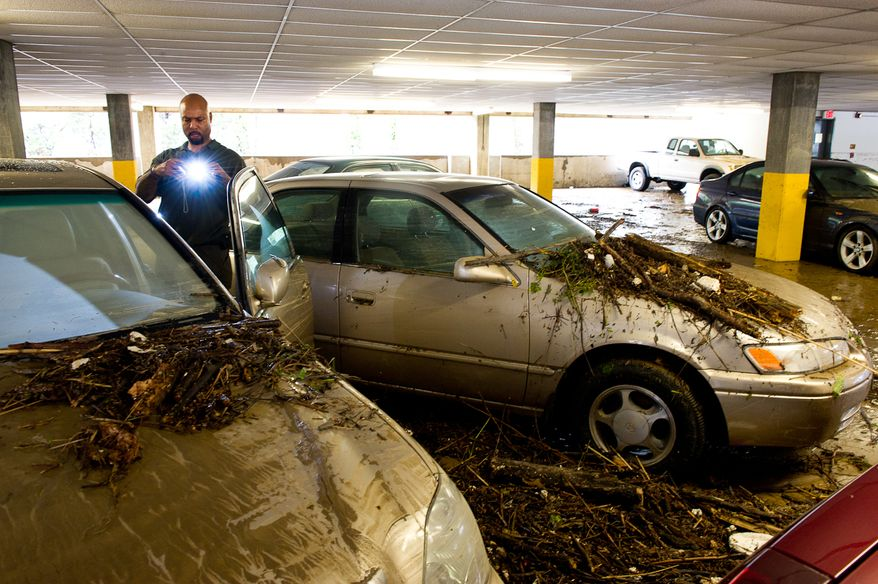 William Borden takes photographs of the flood damage to his Lexus in the parking lot of Strayer University in Alexandria, Va., on Sept. 9, 2011. The lot was flooded after heavy rains pounded the region the previous night. (Andrew Harnik/The Washington Times)