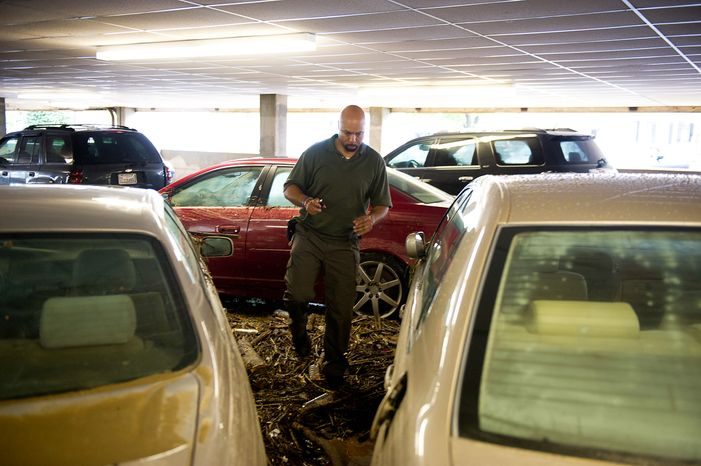 William Borden looks at the flood damage to his Lexus in the parking lot of Strayer University in Alexandria, Va., on Sept. 9, 2011. The lot was flooded after heavy rains pounded the region the previous night. (Andrew Harnik/The Washington Times)