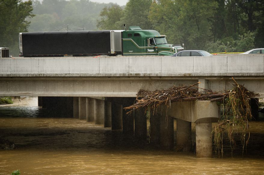Debris is trapped Sept. 9, 2011, on an Interstate 495 bridge over Camden Run near Eisenhower Avenue in Alexandria, Va., which was flooded after heavy rains pounded the region. (Andrew Harnik/The Washington Times)