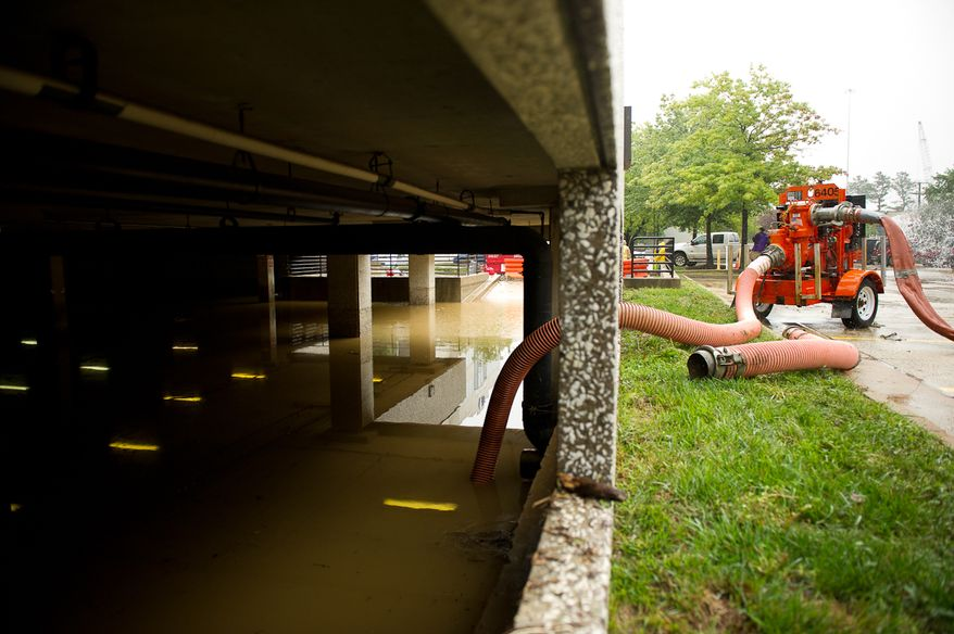 A large gas-powered water pump is employed Sept. 9, 2011, in the basement parking lot under the Alexandria Tech Center 4 on Eisenhower Avenue in Alexandria, Va. The lot was flooded after heavy rains pounded the region the previous night. (Andrew Harnik/The Washington Times)