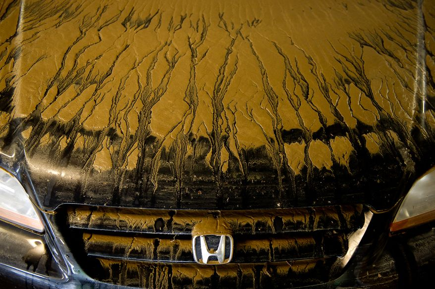 Mud dries on the hood of a car parked on Eisenhower Avenue in Alexandria, Va., on Sept. 9, 2011, after heavy rains pounded the region the previous night. (Andrew Harnik/The Washington Times)