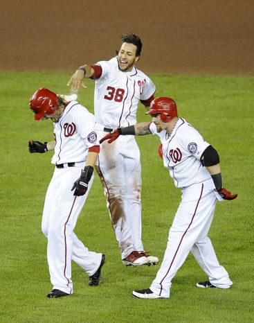 Washington Nationals' Michael Morse celebrates by throwing a rosin bag at teammate Jayson Werth, left, with Jonny Gomes looking on after defeating the Houston Astros 4-3 in 11 innings on Friday, Sept. 9, 2011, in Washington. (AP Photo/Nick Wass)