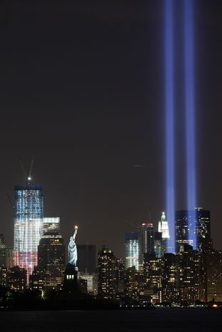 The Tribute in Light shines above lower Manhattan, the Statue of Liberty, and One World Trade Center, left, Saturday, Sept. 10, 2011, in New York. Sunday will mark the 10th anniversary of the Sept. 11, 2001, attacks on the United States. (AP Photo/Mark Lennihan)