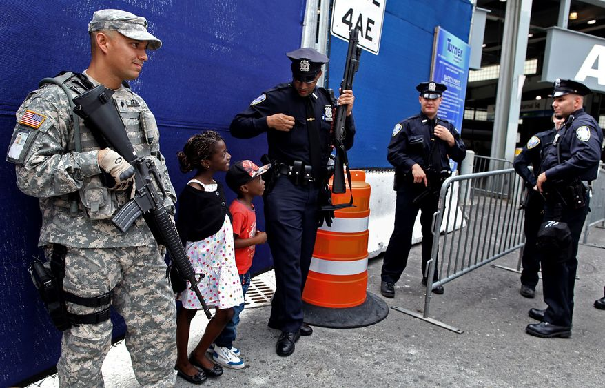 A Port Authority police officer shares a light moment with children visiting from France at commuter train station near ground zero Saturday, Sept. 10, 2011, in New York. Heavily armed police remained a visible presence around New York on the eve of the 10th anniversary of the World Trade Center attacks. (AP Photo/Craig Ruttle)